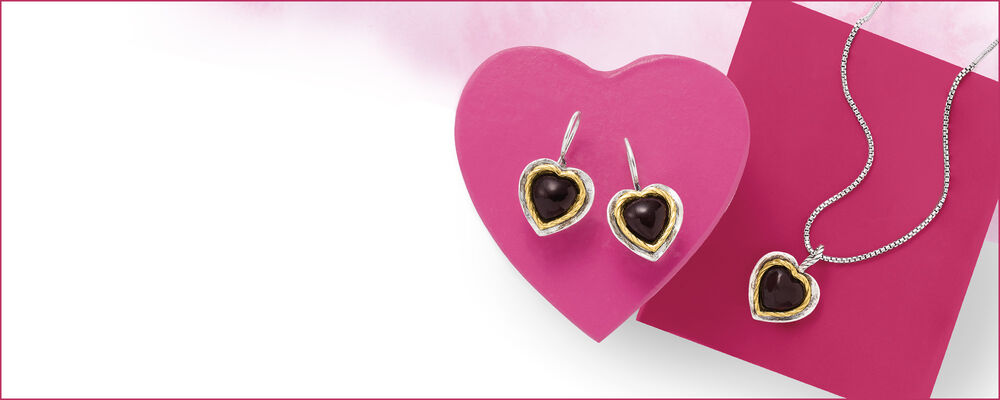 heart-shaped jewelry photographed on a pink heart background. features a pair of garnet heart earrings framed in sterling silver and 14kt yellow gold as well as a matching pendant necklace