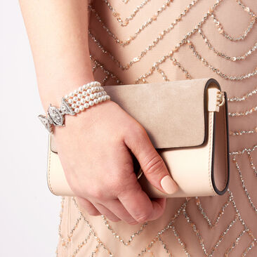 Your mom's moment. Major style for the mothers. Mom holding pocketbook wearing pearl bracelet.