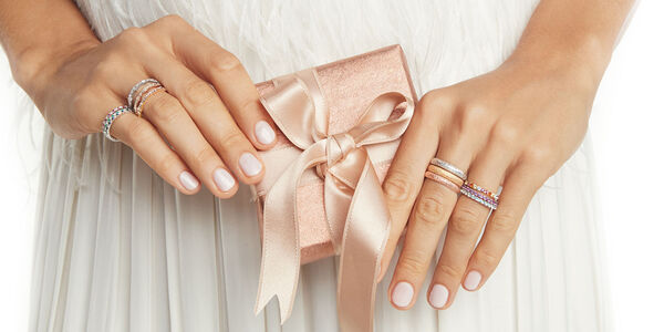 Model Wearing Multiple Wedding Rings Holding Gift Box'