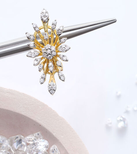 Handcrafted Designs. Image of loose diamonds and jewelry tool holding pendant.