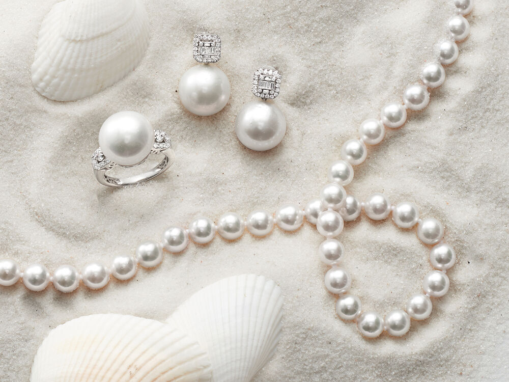 Pearl ring, earrings and strand necklace on sand with seashells.