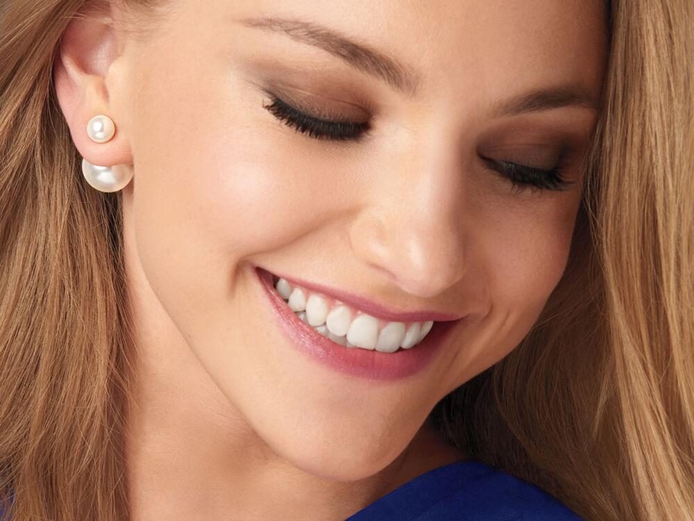 Smiling model wearing front/back pearl earrings.