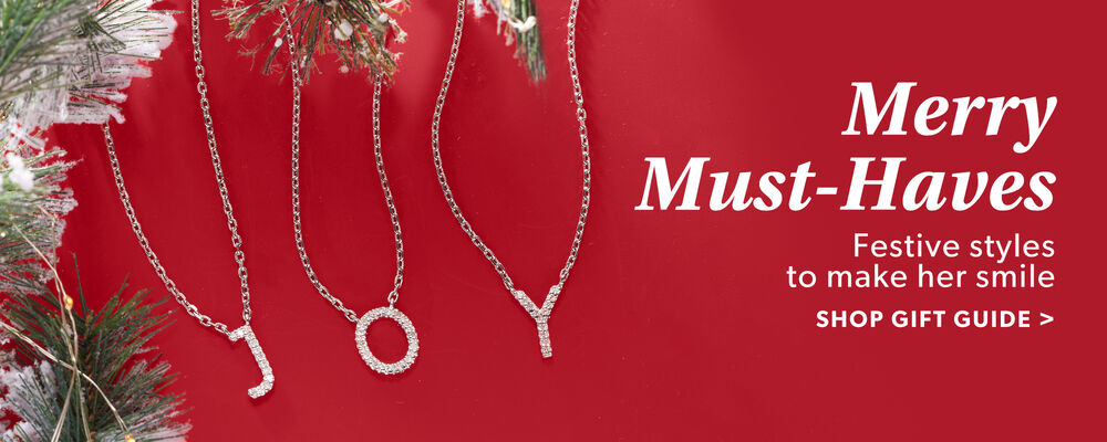 Merry Must-Haves. Feastive Styles To Make Her Smile. Shop Gift Guide. Image Featuring Necklaces that spell-out Joy on Red Background With Snow And Greens