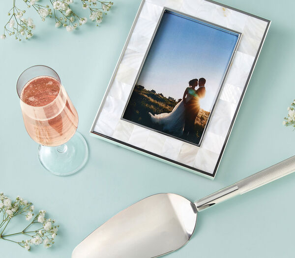 Wedding Gifts. Special somethings for a day they'll never forget. Image of picture frame, champagne glass and cake knife.
