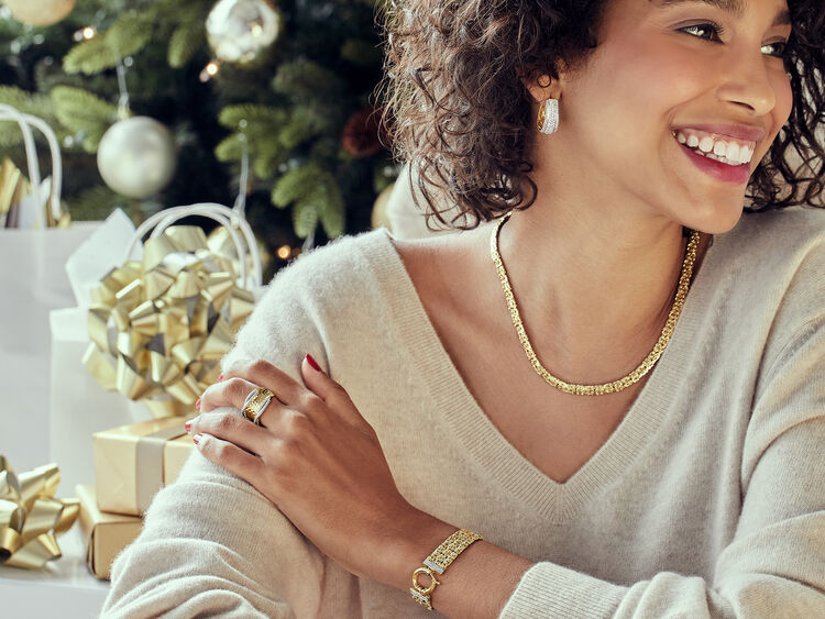 Model wearing gold necklace, ring and bracelet.