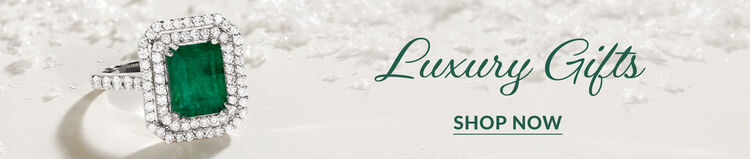 Luxury Gifts. Shop Now. Image featuring diamond and gemstone ring on white snow background