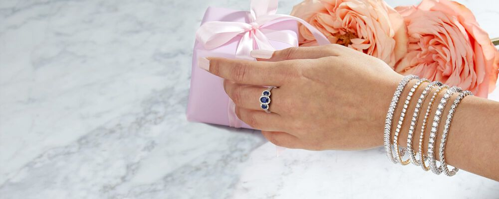 Image of a hand reaching for a gift, wearing multiple diamond tennis bracelets and a blue three-stone ring, on marble background