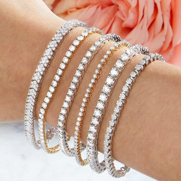 multiple diamond tennis bracelets stacked on a womans wrist