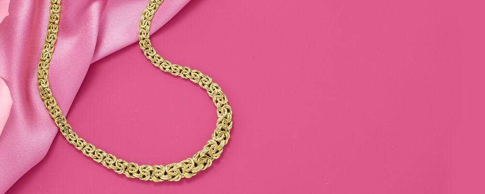 gold byzantine-style necklace on a pink background