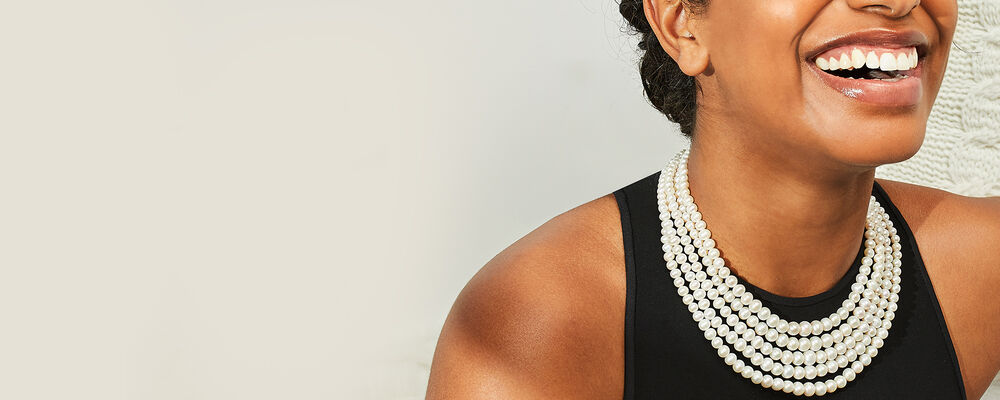 Classics. Timeless Fashions for Every Day. Model Shot Wearing a Pearl Necklace